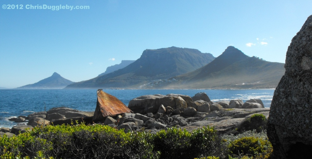 Shipwreck near Sandy Bay Beach in front of Cape Town Mountains