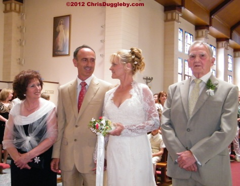 Bride and groom together at the altar with their proud parents