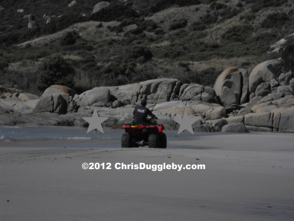 Police on Quadbike dealing with a couple of stars bathing on Sandy Bay Beach Cape Town
