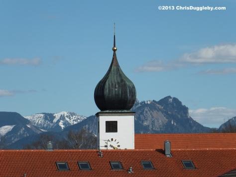 Blue skies over Bad Feilnbach's Pfarrkirche Herz Jesu - against the magnificent Alpine mountains