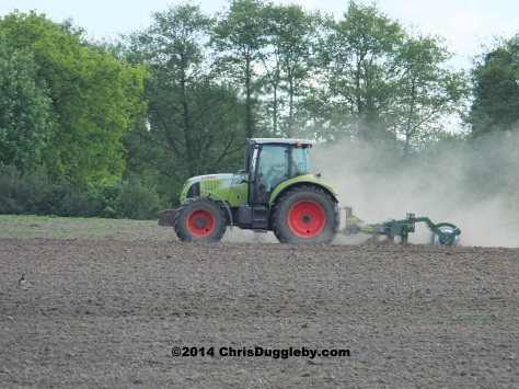 Farmer Ploughing Fields With Tractor Near Footpath