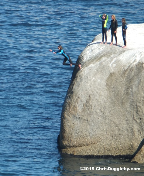 3 Four Cape Town Girls in Wetsuits jumping off Sunset Rocks
