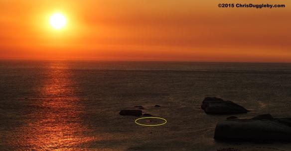 4 Canoeist (highlighted) paddling past Sunset Rocks at Sunset