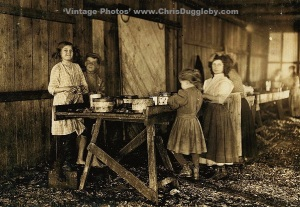 Young Oyster Pickers working through the lunch period at Peerless Oyster Co., Bay St Louis, Mississippi, USA (1911)