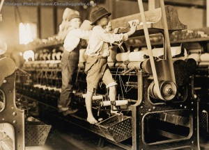 Young boys mend broken threads on spinning looms in a Mill at Macon, Georgia, USA (1909)